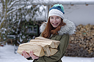 Portrait of smiling teenage girl carrying firewood in winter - LBF01569