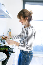 Young woman cooking vegan pasta in her kitchen - VABF01177