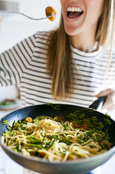 Young woman holding pan with vegan pasta dish - VABF01183