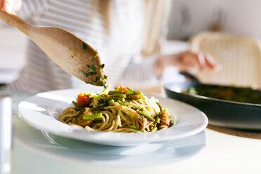 Young woman serving vegan pasta dish - VABF01186