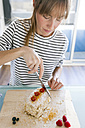 Young woman cutting up vegan cake - VABF01195