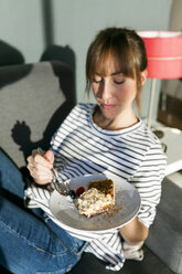 Young woman eating piece of vegan cake - VABF01198