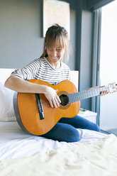 Young woman playing guitar, sitting on bed - VABF01201