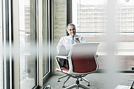 Senior manager in office sitting on chair talking on the phone - UUF09936