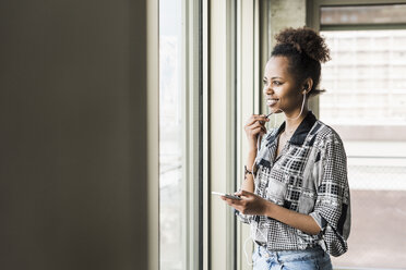 Young woman standing at window using smart phone - UUF09951