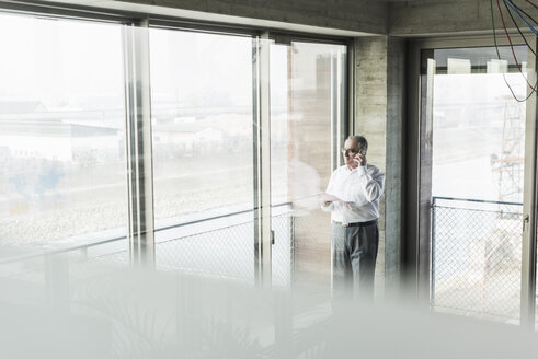 Senior manager in office standing at window, talking on the phone - UUF09954