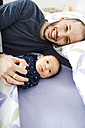 Happy father lying in bed with his  newborn baby girl - GEMF01477