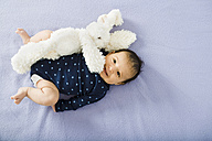 Happy newborn baby girl on bed with a stuffed rabbit - GEMF01483