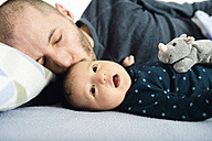 Father kissing his newborn baby girl on bed - GEMF01486