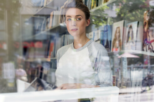 Young woman in a bookshop looking through window - LMF00612