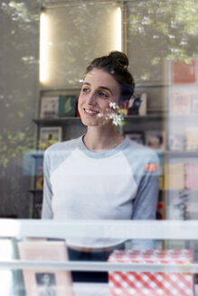 Portrait of smiling young woman in a bookshop looking through window - LMF00615