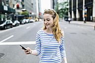 USA, New York, Manhattan, Young woman walking in the street, holding mobile phone - GIOF01889