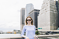 USA, New York City, Young woman standing in Manhattan at railing, holding smart phone - GIOF01910