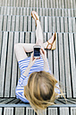 Young woman sitting at pier using mobile phone - GIOF01916