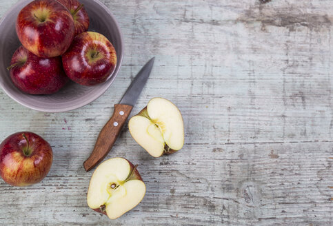 Whole and sliced red apples and a kitchen knife on wood - JUNF00856