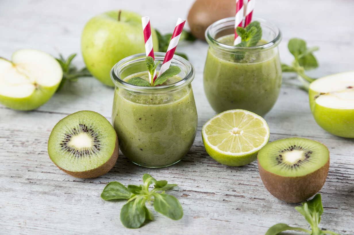 Two glasses of green smoothie and ingredients on wood - JUNF00859 - JLPfeifer/Westend61