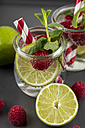 Glass of detox water with limes and rasperries decorated with mint leaves - JUNF00868