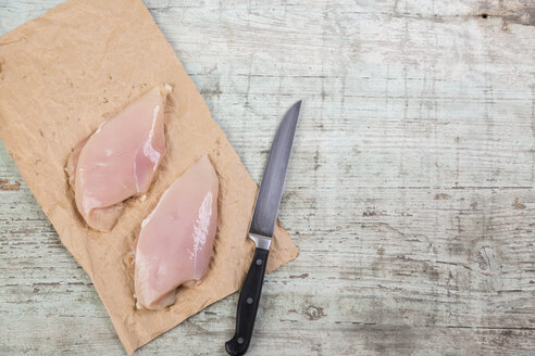 Chicken breast on brown paper and a knife - JUNF00883