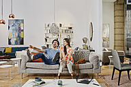 Couple in modern furniture store testing couch, being happy - RORF00577