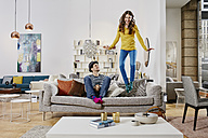 Couple in modern furniture store jumping on couch - RORF00586