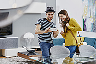 Couple in furniture store looking at dining table, taking pictures with smart phone - RORF00592