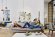Couple in modern furniture store testing couch, being happy - RORF00598