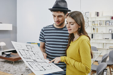 Couple with floor plan choosing furniture in furniture shop - RORF00607