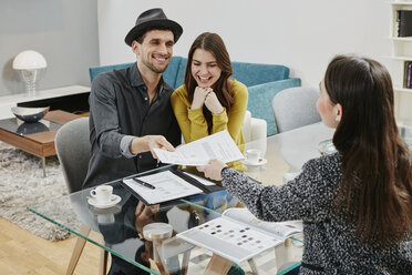 Couple signing sales contract in furniture store - RORF00613