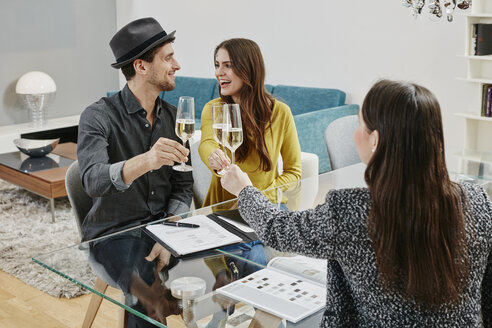 Couple celebrating sales contract in furniture store - RORF00616