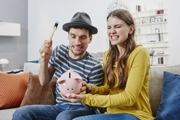 Couple in furniture store demolishing piggy bank - RORF00619