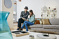 Couple choosing furniture in shop, using digital tablet - RORF00631