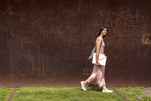Smiling young woman walking in front of corten wall - LMF00633