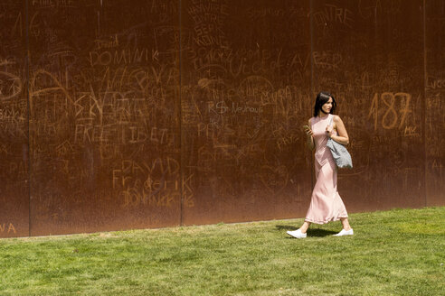 Young woman walking in front of corten wall - LMF00636