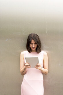 Young woman leaning against metal wall using tablet - LMF00645