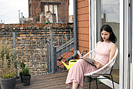 Young woman reading newspaper on roof terrace - LMF00660