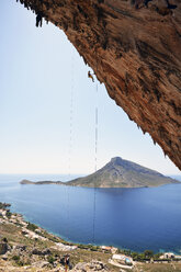 Greece, Kalymnos, climber abseiling in rock wall - LMF00671