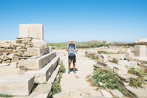 Greece, Mykonos, Delos, tourist looking at map at archaeological site - GEMF01497