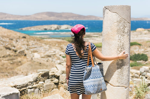Greece, Mykonos, Delos, tourist at archaeological site enjoying the view - GEMF01503