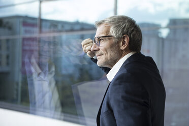 Confident businessman looking out of window - RBF05614