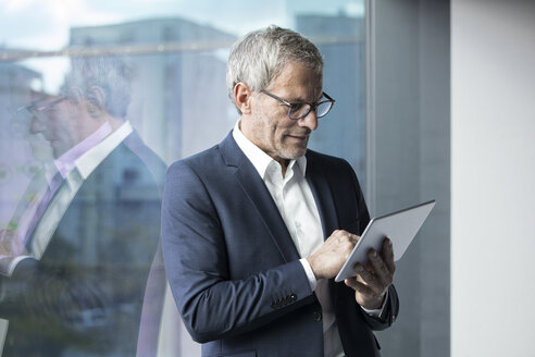 Businessman using tablet at the window - RBF05617