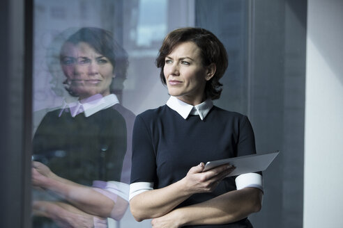 Pensive businesswoman holding tablet looking out of window - RBF05620