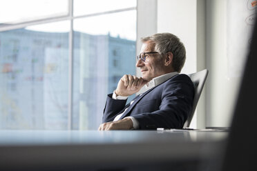 Confident businessman looking out of window - RBF05629
