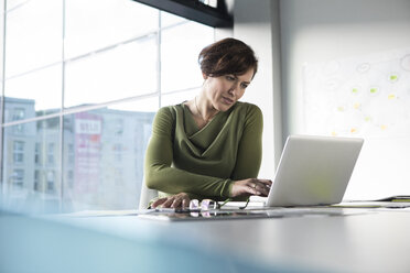 Businesswoman using laptop in office - RBF05635