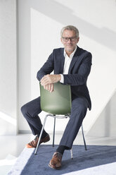 Confident businessman sitting on chair - RBF05638