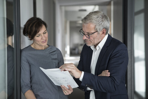 Businessman and businesswoman discussing document in office - RBF05650