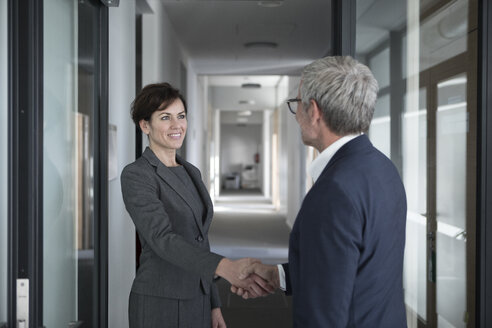 Businessman and businesswoman shaking hands in office - RBF05653