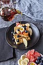 Pouring maple sirup on waffles with various fruits - SARF03188