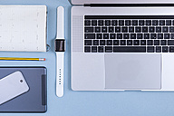 Various electronic devices, personal organizer and a pencil on blue ground - MMAF00028