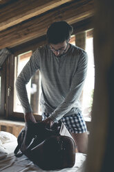 Young man making luggage for travel on bed - ZOCF00150