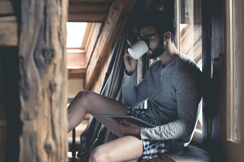 Young man using tablet and drinking coffee at home - ZOCF00159